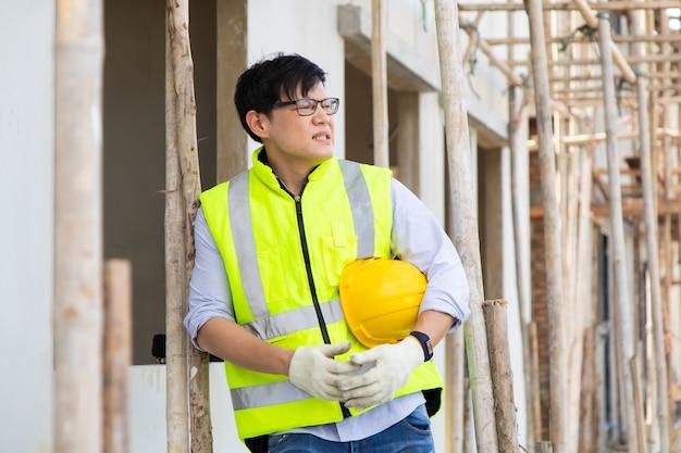 Trabajador de la construcción del hombre asiático que parece estresado en el sitio de construcción.