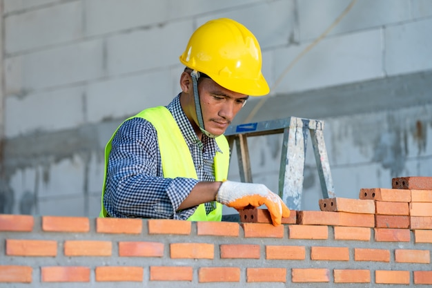 Trabajador de la construcción instalando ladrillo rojo con espátula llana para la construcción de viviendas nuevas en el sitio de construcción