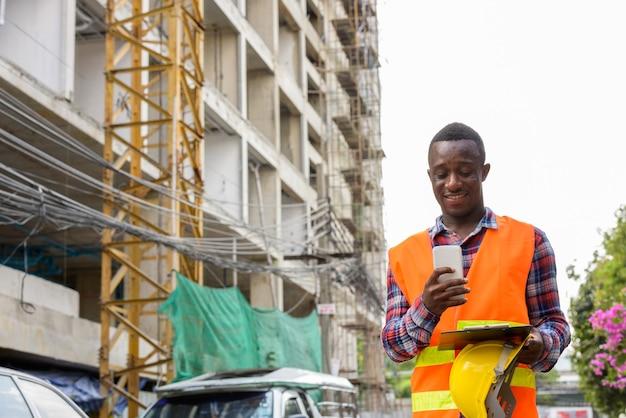 Trabajador de la construcción joven africano negro feliz sonriendo y nosotros