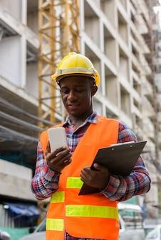 Trabajador de la construcción joven africano negro feliz sonriendo