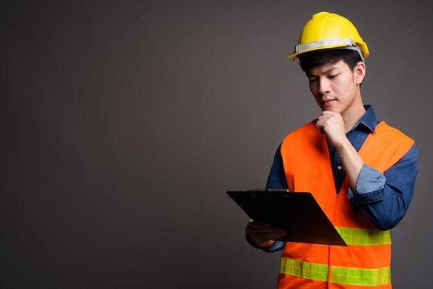 Trabajador de la construcción joven apuesto hombre asiático en gris