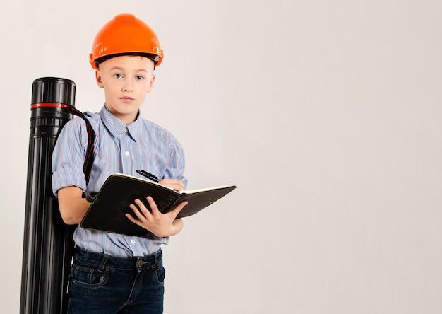 Trabajador de construcción lindo que sostiene el cuaderno