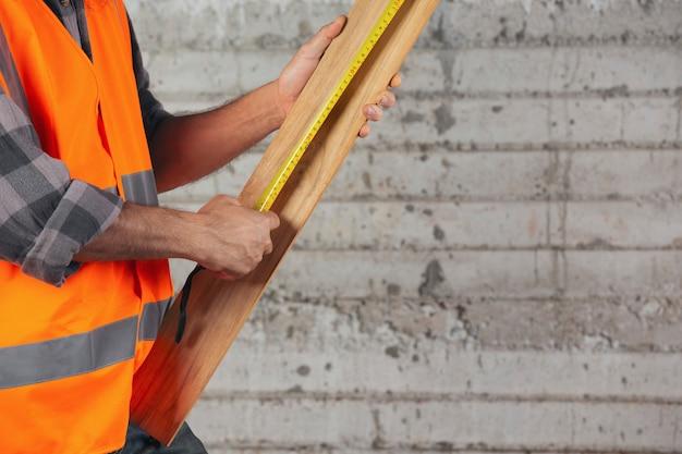 Trabajador de la construcción lleva tablones de madera con cinta métrica en el sitio de construcción.