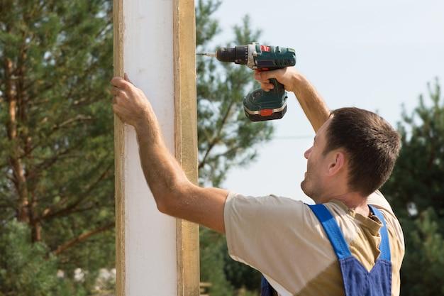 Trabajador de la construcción masculina de cerca perforando sobre una plancha de madera durante la construcción de una casa.