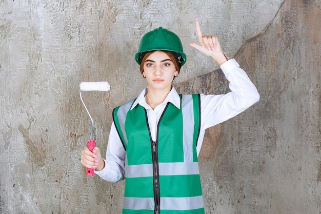 Trabajador de la construcción mujer hermosa con pie de rollo de pintura