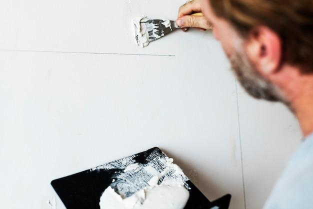 Trabajador de la construcción pintando la pared