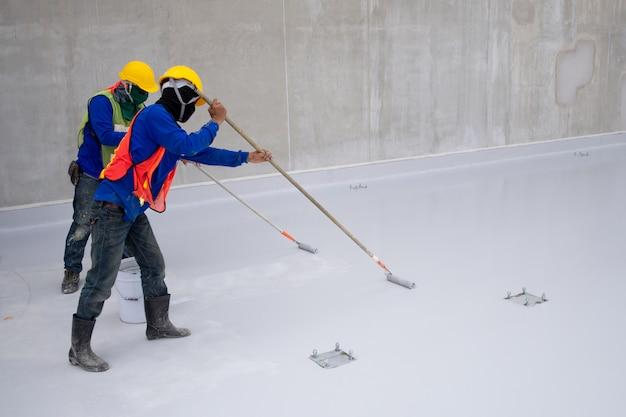 Trabajador de la construcción pintura epoxi en el piso para protección a prueba de agua.