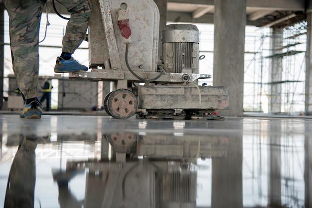 El trabajador de la construcción produce la lechada y termina el concreto húmedo con una herramienta especial.