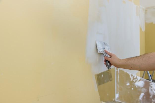 Trabajador de la construcción profesional aplicando revestimiento de yeso a la placa de yeso recién