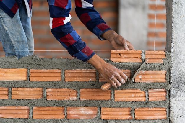 Trabajador de construcción profesional de la mano del primer que pone ladrillos en nuevo sitio industrial