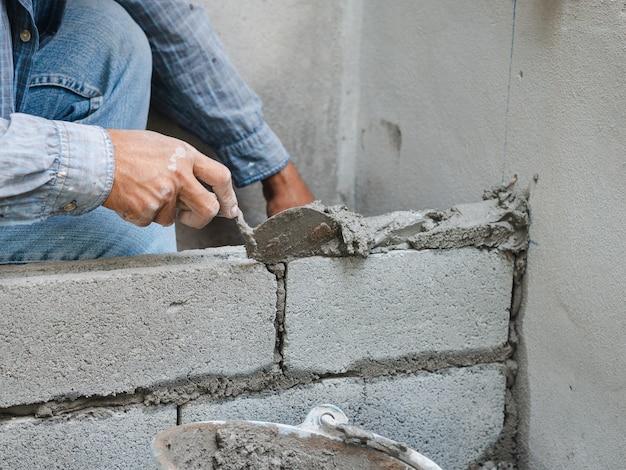 Trabajador de la construcción profesional poniendo ladrillos con cemento.
