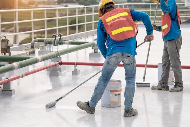 Trabajador de la construcción que cubre la pintura de epoxy en la losa de techo para la protección a prueba de agua