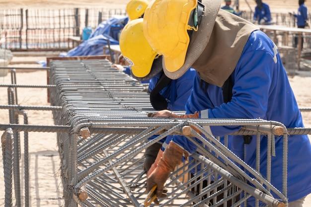 Un trabajador de la construcción que fija la barra de acero en el sitio de construcción