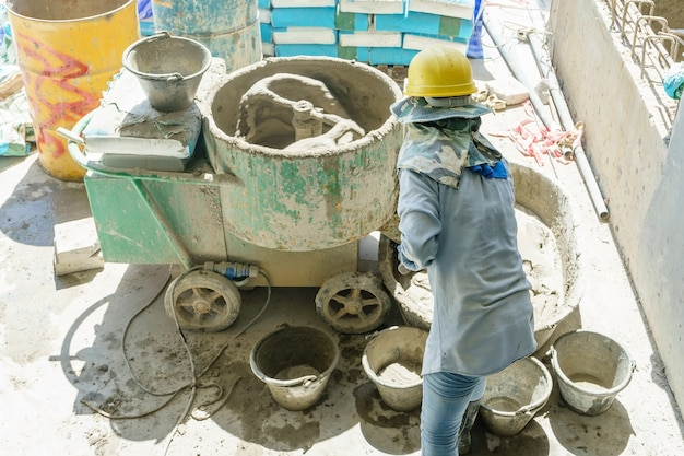 Trabajador de la construcción que mezcla el cemento por la máquina del mezclador de cemento en el sitio de construcción