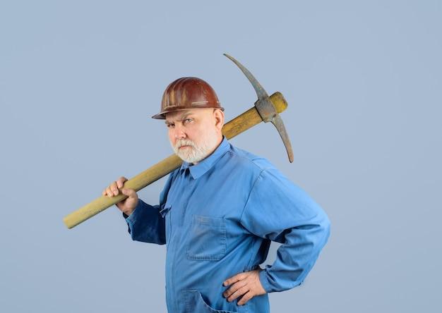 Trabajador de la construcción serio con piqueta obrero con piqueta albañil macho en casco con