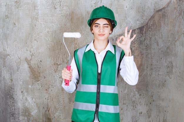 Trabajador de la construcción de sexo femenino hermoso que sostiene el rollo de pintura y que muestra el signo de ok