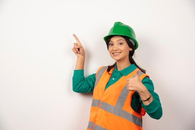 Trabajador de la construcción de sexo femenino joven en el fondo blanco.