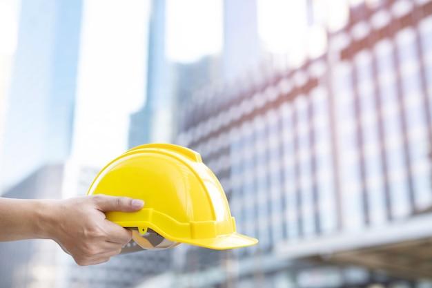 Un trabajador de la construcción de sexo masculino de ingeniería está de pie sosteniendo un casco amarillo de seguridad y usa ropa reflectante para la seguridad de la operación de trabajo
