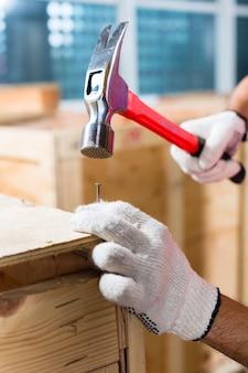 Trabajador de la construcción en un sitio de construcción cerrar una caja de madera o contenedor de carga con un martillo y un clavo