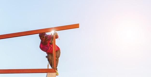 Trabajador de la construcción soldar acero para estructura de techo