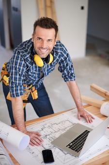 Trabajador de la construcción sonriente con planes y una computadora portátil