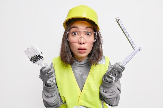 Trabajador de la construcción sorprendido ocupado con la renovación de la casa sostiene pincel de pintura y cinta métrica usa gafas de seguridad de casco y uniforme aislado en blanco
