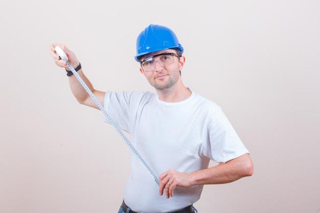 Trabajador de la construcción sosteniendo cinta métrica en camiseta, jeans, casco y mirando alegre