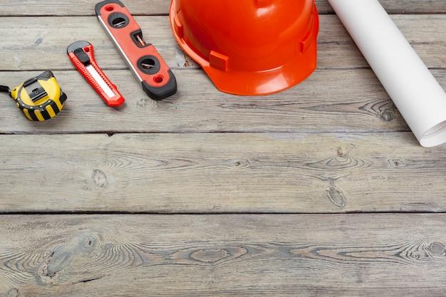 Trabajador de la construcción suministros e instrumentos en el fondo de la mesa de madera