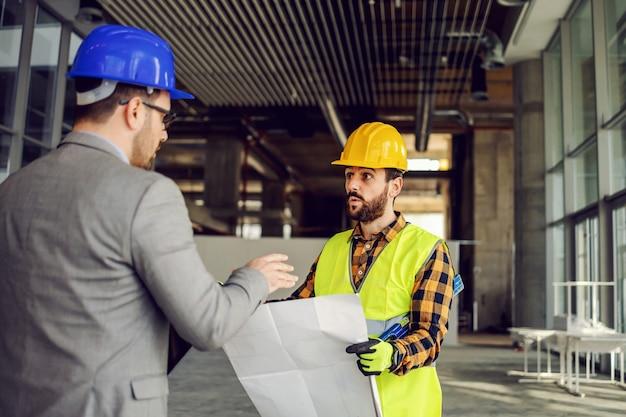 Trabajador de la construcción y supervisor discutiendo sobre obras en el sitio