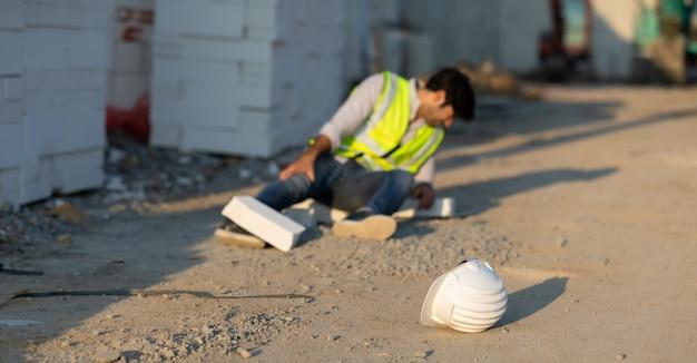 Trabajador de la construcción tiene un accidente tirado en el suelo mientras trabajaba en el sitio de construcción accidente en el trabajo