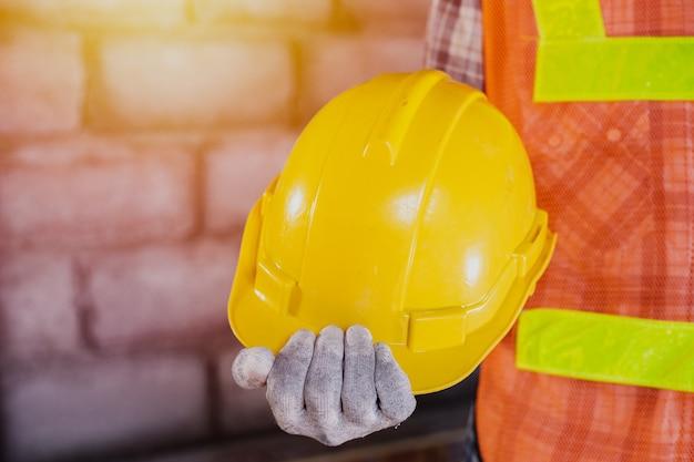 Trabajador de la construcción, trabajador con herramienta sobre fondo de construcción.