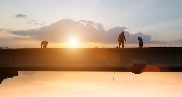 Trabajador de la construcción trabajando con puesta de sol