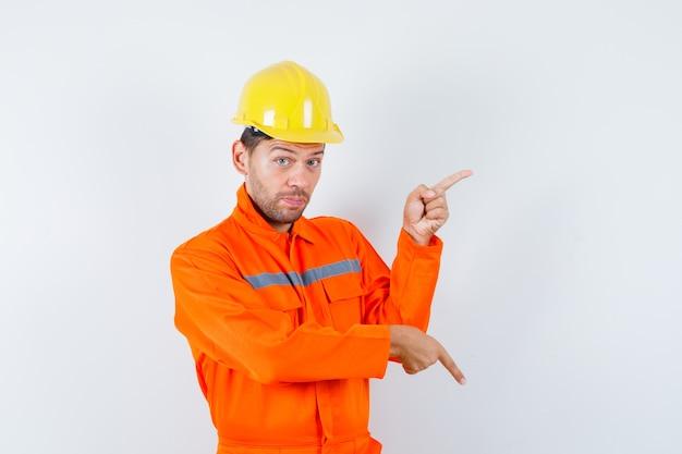Trabajador de la construcción en uniforme, casco apuntando con el dedo hacia arriba y hacia abajo y mirando indeciso, vista frontal.