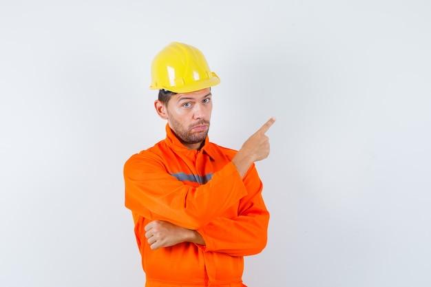Trabajador de la construcción en uniforme, casco apuntando a la esquina superior derecha y mirando confiado, vista frontal.