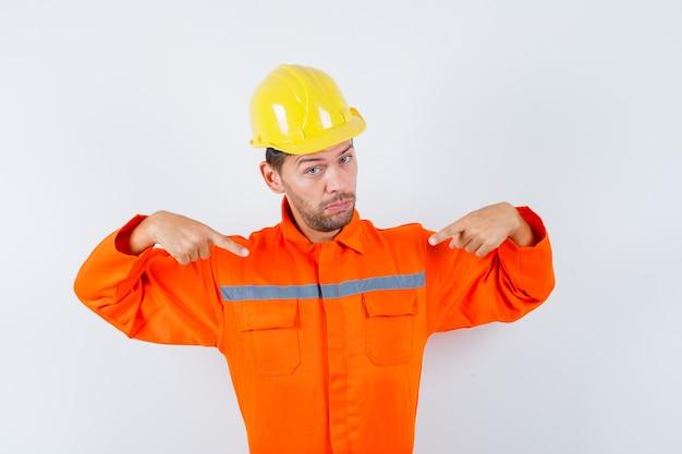 Trabajador de la construcción en uniforme, casco apuntando a sí mismo y mirando confiado, vista frontal.