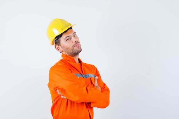 Trabajador de la construcción en uniforme, casco de pie con los brazos cruzados y mirando confiado, vista frontal.