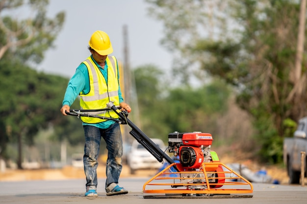 Un trabajador de la construcción vertiendo un concreto húmedo en el sitio de construcción de carreteras