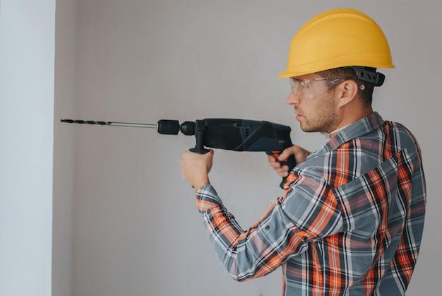 Trabajador constructor con equipo haciendo agujero en la pared en el sitio de construcción