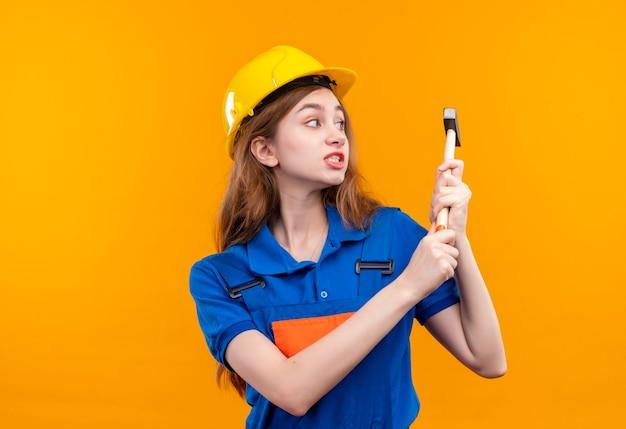 Trabajador constructor joven en uniforme de construcción y casco de seguridad columpio parado sobre pared naranja