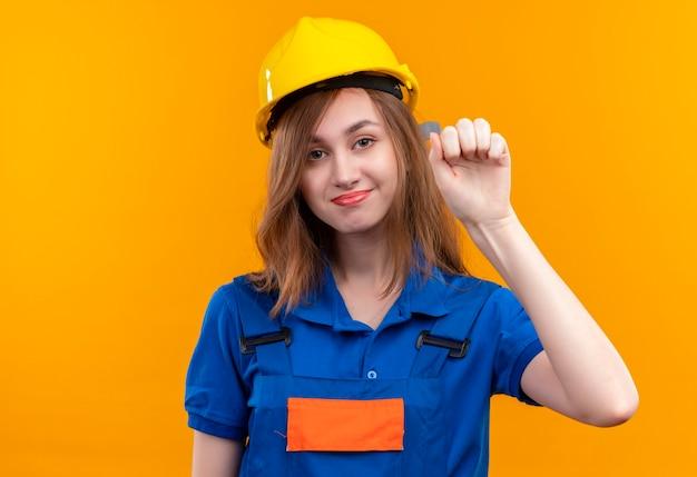 Trabajador constructor joven en uniforme de construcción y golpeando el casco de seguridad