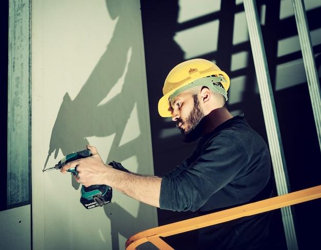 Trabajador construye una pared de placas de yeso.