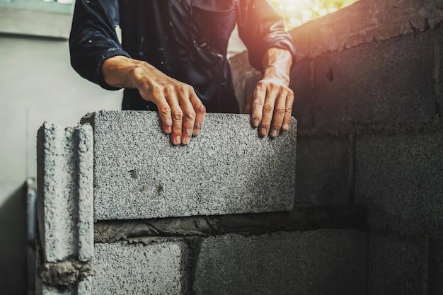 Trabajador construyendo ladrillos de pared con cemento