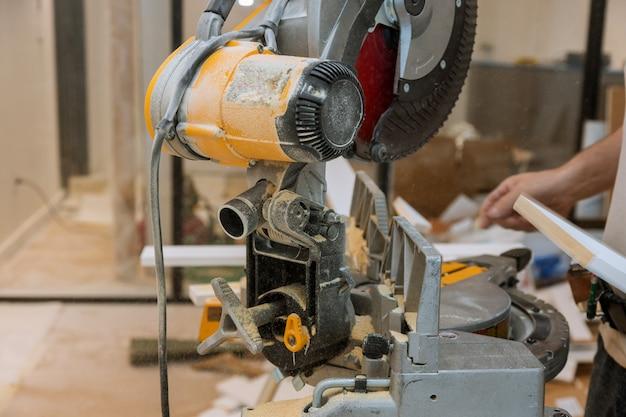 Trabajador corta el zócalo de molduras de madera en la sierra de ingletes