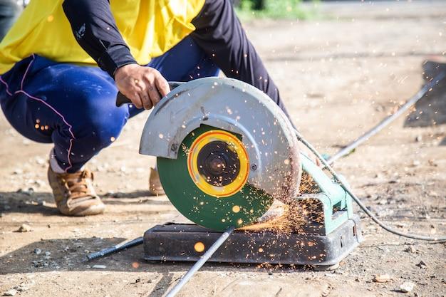 Un trabajador cortando acero con un cortador circular de acero. hay chispas al cortar en un sitio de construcción.