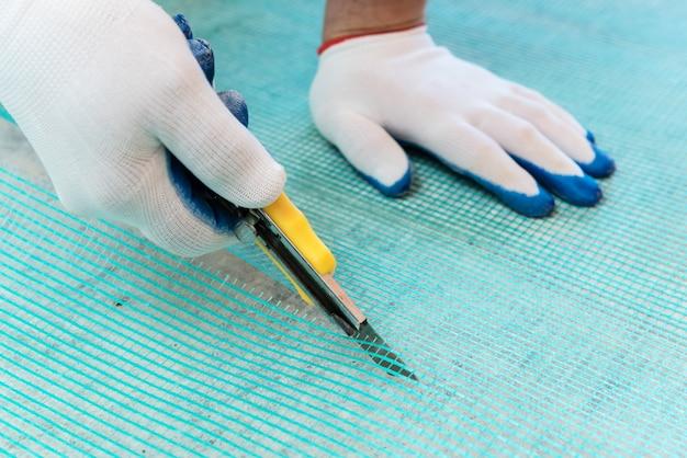 Un trabajador está cortando una malla de fibra de vidrio.