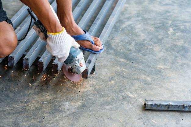 Trabajador cortando metal con molinillo con chispas.