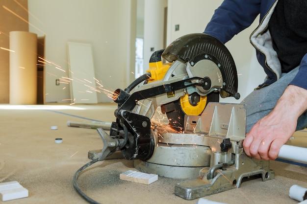Trabajador de corte de metal con molinillo. chispas mientras se muele el hierro