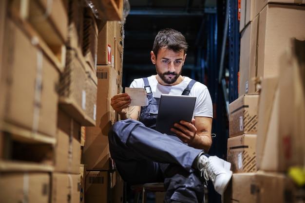Trabajador de cuello azul trabajador serio joven con un mono sentado en una silla en el almacenamiento rodeado de cajas y comprobando la entrega en la tableta. interior de empresa de importación y exportación.