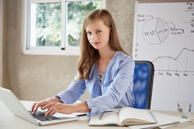 Trabajador de cuello blanco escribiendo en el teclado y mirando a cámara
