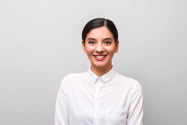 Trabajador de cuello blanco joven y atractiva morena en camisa blanca con labios rojos, maquillaje de negocios y pelos atados